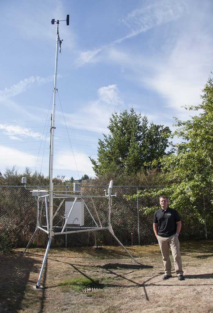 Katherine Engqvist Aug. 25/15- Alan DeCiantis, director of product management at Forest Technology Systems Ltd. stands beside one of their remote automated weather stations to give an idea of it's scale. The Langford-based company is the backbone of fire weather technology in North America.